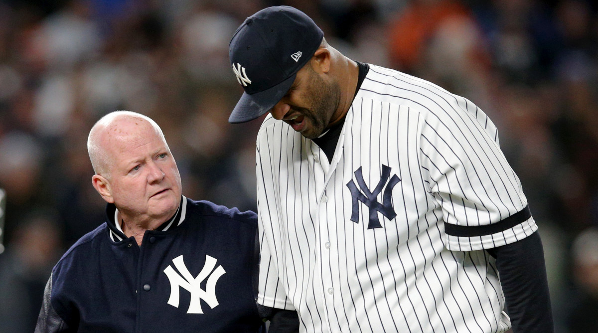 Oct 17, 2019; Bronx, NY, USA; New York Yankees pitcher CC Sabathia (52) is walked off the field by trainer Steve Donohue after suffering an apparent injury against the Houston Astros during the eighth inning of game four of the 2019 ALCS playoff baseball series at Yankee Stadium. Mandatory Credit: Brad Penner-USA TODAY Sports