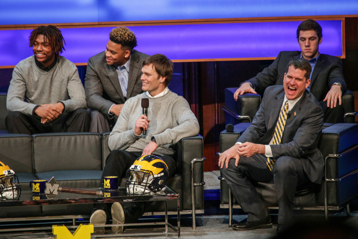 """Brandon Peters (back right) looks on as head coach Jim Harbaugh (front right) and New England Patriots quarterback Tom Brady (center) have a laugh during the special event, """"Signing of the Stars,"""" on Michigan's campus."""