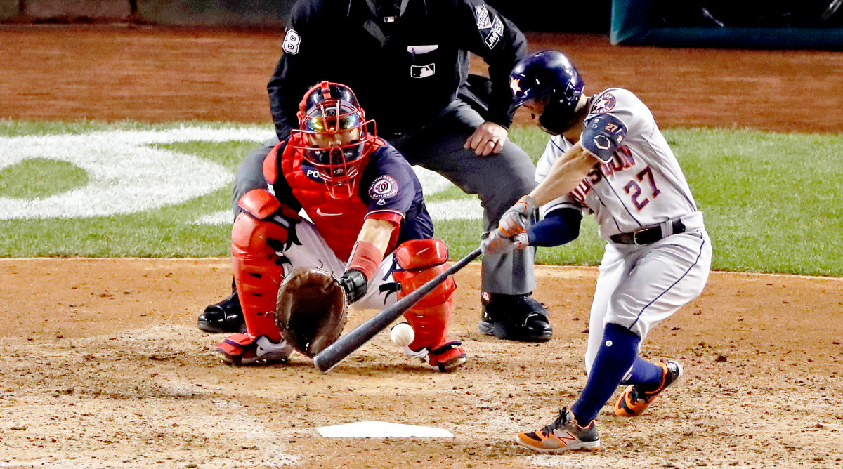 Oct 25, 2019; Washington, DC, USA; Houston Astros second baseman Jose Altuve (27) hits a double during the fifth inning against the Washington Nationals in game three of the 2019 World Series at Nationals Park. Mandatory Credit: Geoff Burke-USA TODAY Sports