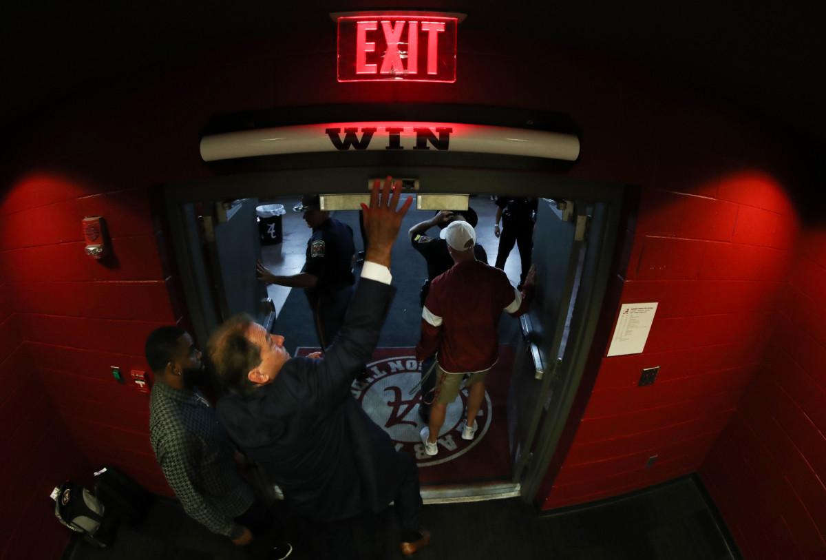 "Nick Saban hits the Alabama ""Win"" bar above the locker room door"