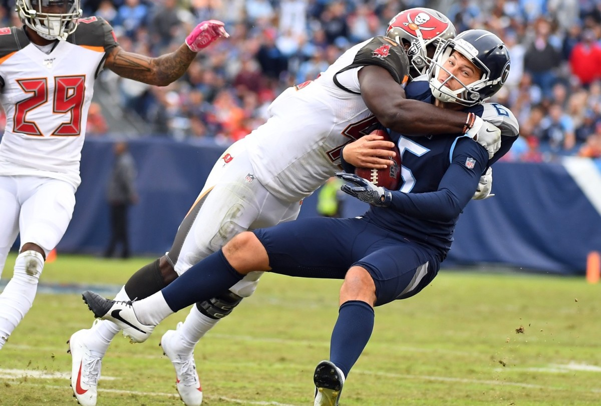 Tennessee Titans punter Brett Kern (6) is tackled by Tampa Bay Buccaneers linebacker Devin White (45) on a fake field goal attempt during the second half at Nissan Stadium.
