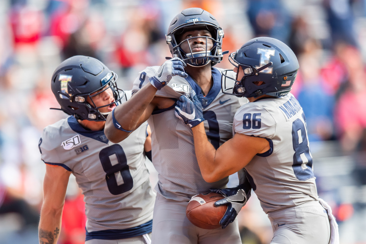 Illinois wide receiver Josh Imatorbhebhe (9) celebrates a touchdown with wide receiver Casey Washington (8) and wide receiver Donny Navarro (86) during a game against Wisconsin at Memorial Stadium.