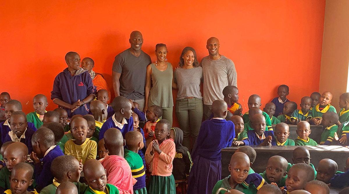 Anthony Lynn (left, standing), Stacey Lynn, Danielle Lynn and D'Anton Lynn stand in a classroom of the school.