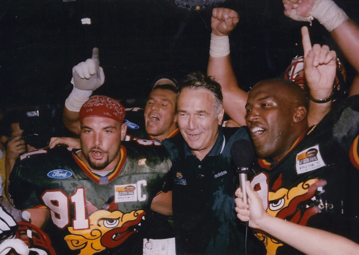 Naposki celebrates with Barcelona Dragons coach Jack Bicknell (center) and other teammates after their 1997 World Bowl victory.