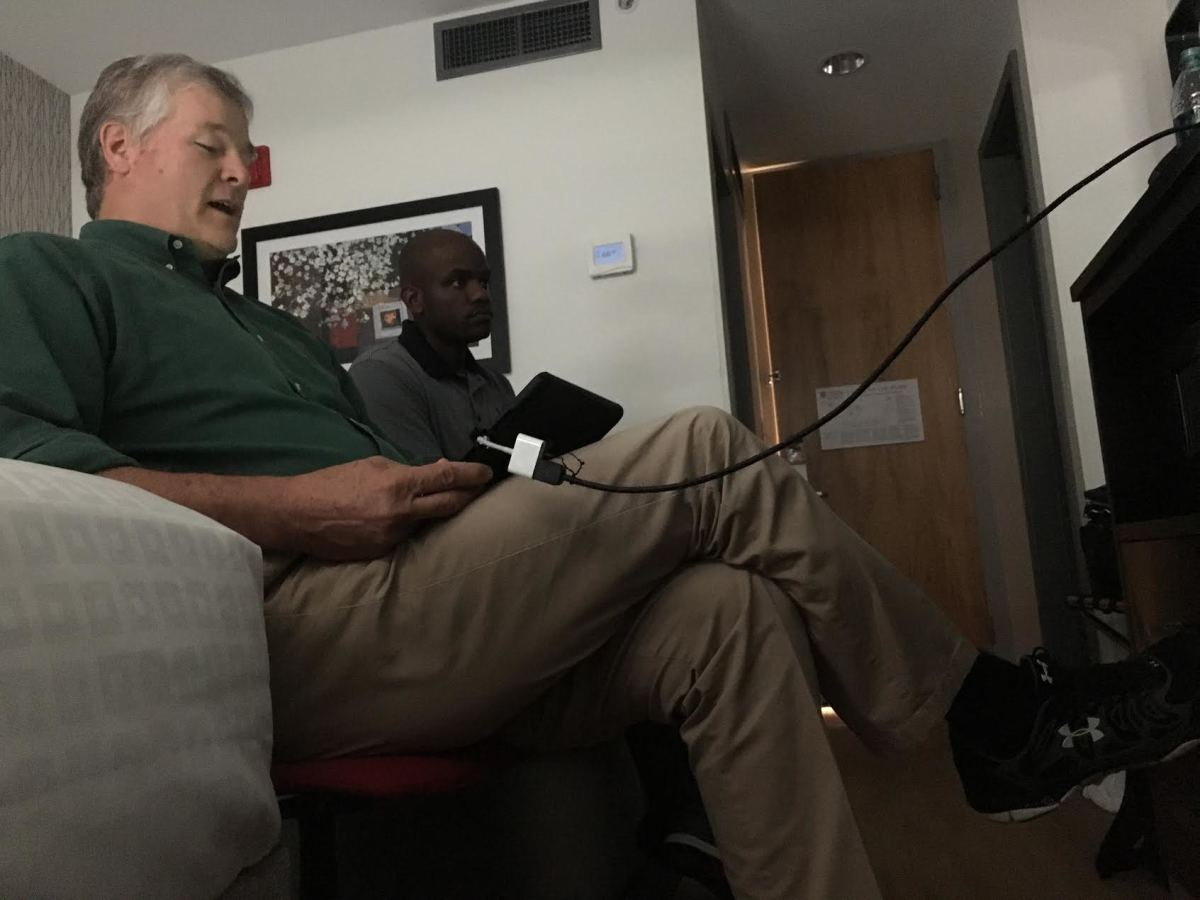 Russ Pulley, an 18-year veteran of SEC officiating, reviews plays on an iPad connected to a TV from a room at the University of Georgia Hotel.