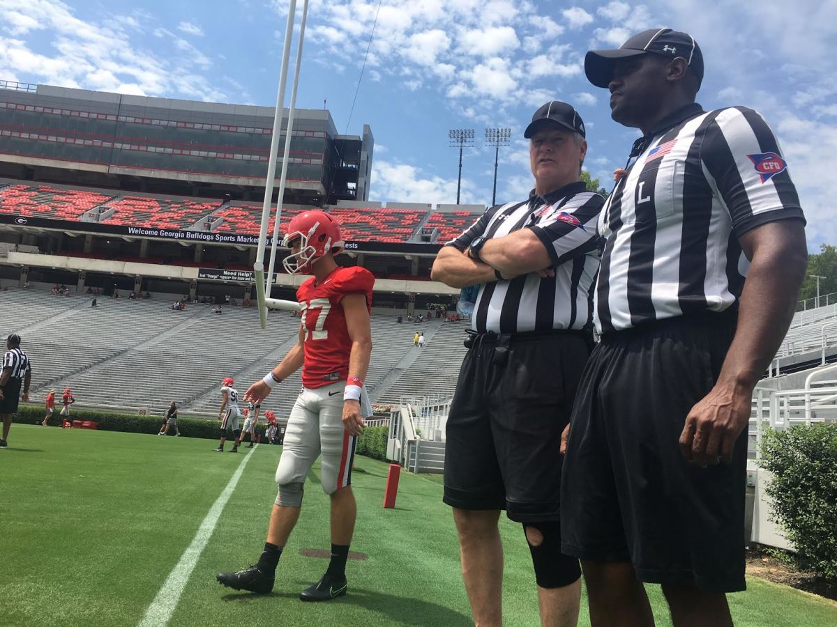 Russ Pulley and Walter Flowers, two SEC officials, talk with one another ahead of Georgia camp scrimmage earlier this month. A UGA specialist is in the background warming up.