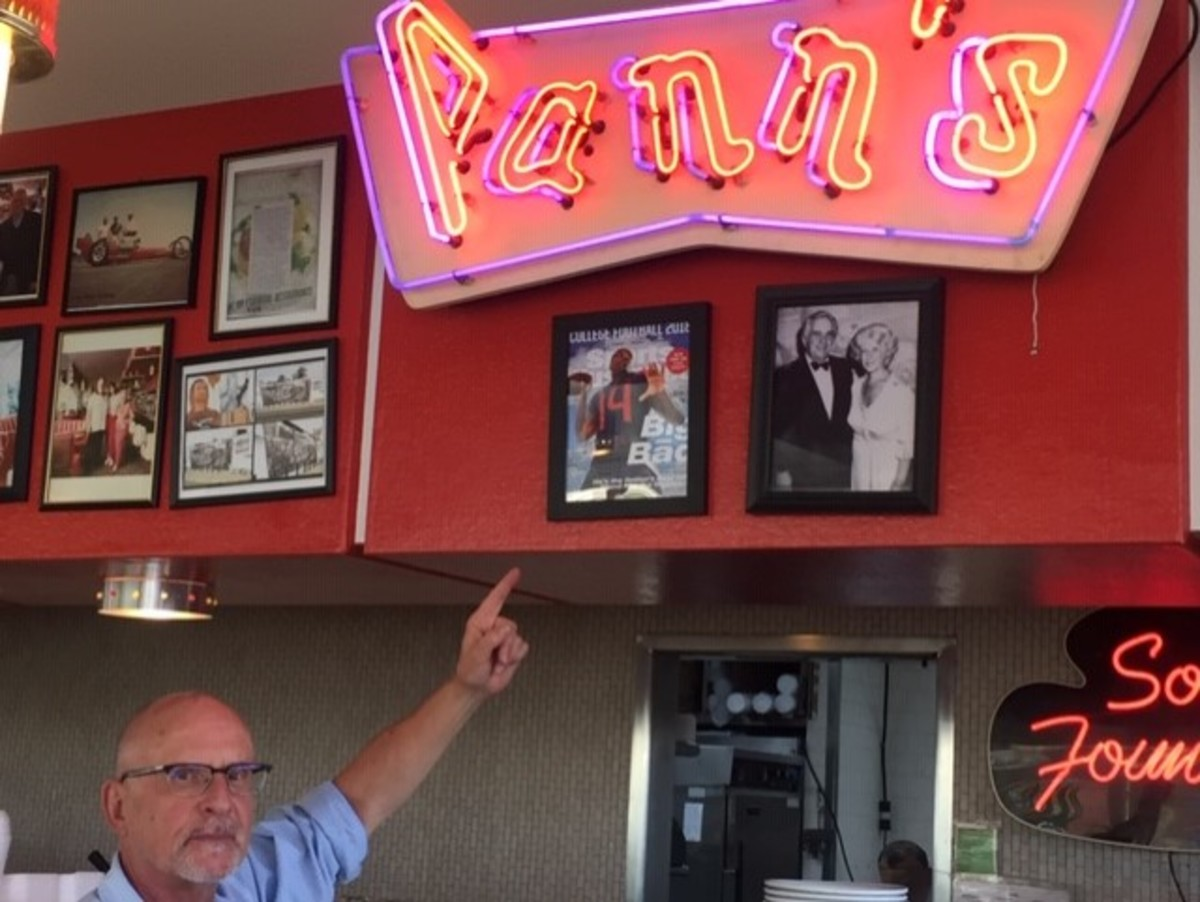 Jim Poulos, the owner of Pann's Restaurant in Los Angeles, points at the August 2018 Sports Illustrated regional cover picturing a neighborhood kid, LA-born Arizona quarterback Khalil Tate.