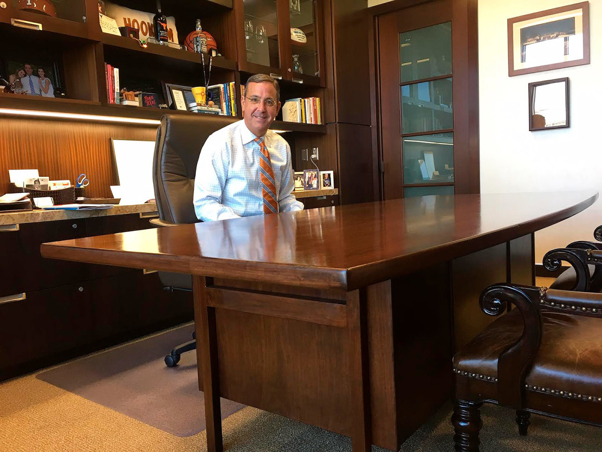Texas athletic director Chris Del Conte smiles from behind his office desk, the same one used by Darrell Royal around 60 years ago.