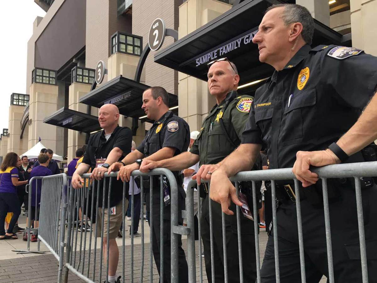 Three of LSU's four game day law enforcement supervisors watch as fans file into Tiger Stadium through new metal detectors. LSU Police Chief Bart Thompson, far right, stands next to East Baton Rouge Parish Maj. Todd Morris and LSU Police Maj. Marshall Walters.