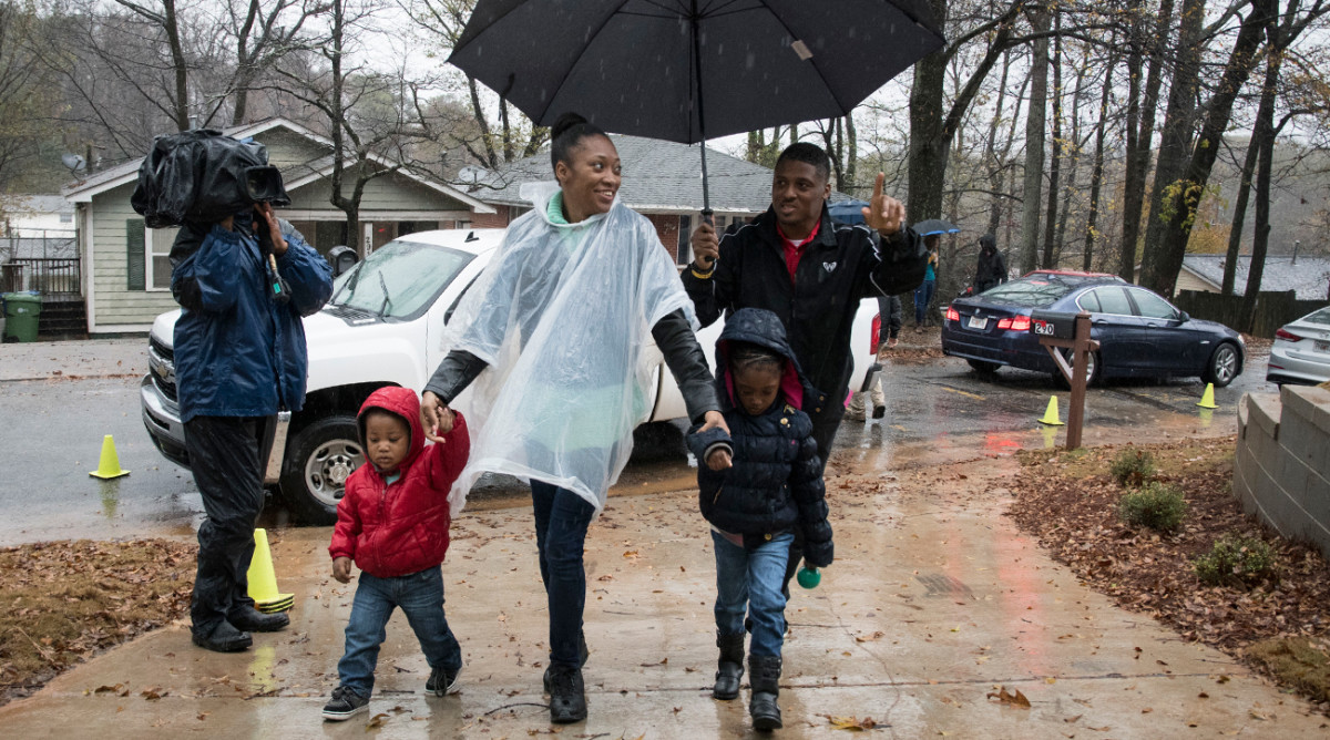 Dunn escorts a family into their new house in December, the 159th that his Home for the Holidays charity has provided for single moms and their kids.