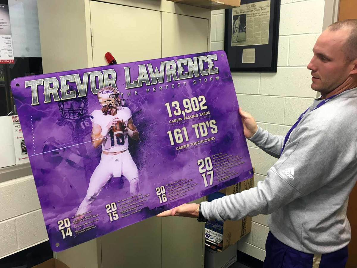 Cartersville High coach Joey King holds an illustration he had made of Trevor Lawrence's accomplishments in four years as Cartersville's starting quarterback.