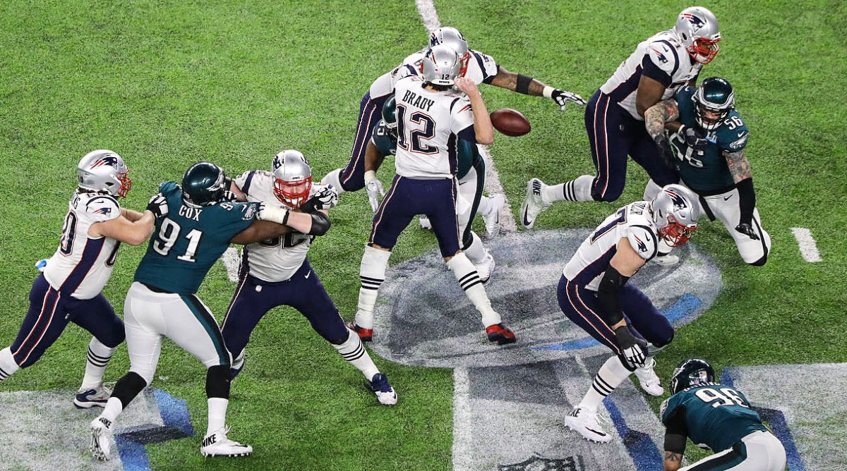 Brandon Graham pokes the ball out of Tom Brady's grip, a pivotal moment in Super Bowl LII.