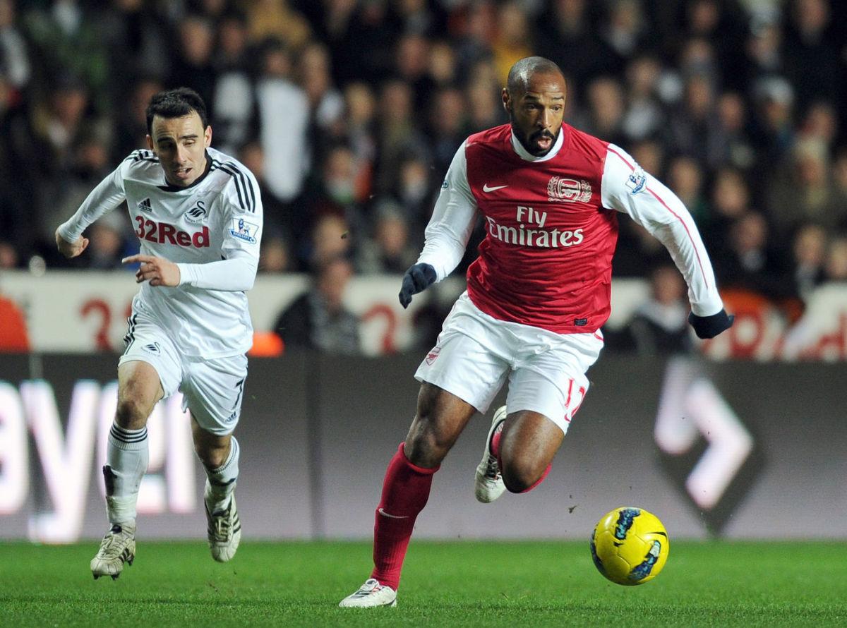 Swansea City's Leon Britton (L) chases a