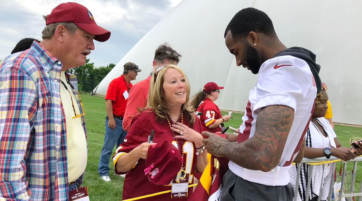 Longtime Washington fan Gene Bogley and his fiancée Donna Late—wearing her No. 11 Alex Smith jersey—take in the team's minicamp practice.