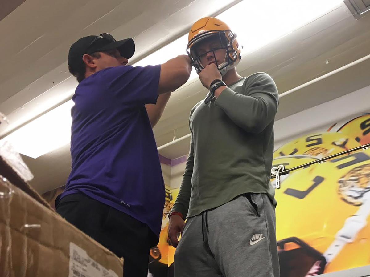 Equipment director Greg Stringfellow fits Ohio State transfer Joe Burrow with his new LSU helmet.