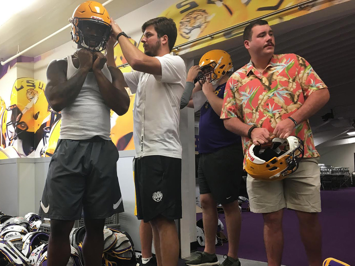 Student manager Kiley Greathouse helps edge rusher K'Lavon Chaisson with his new helmet.