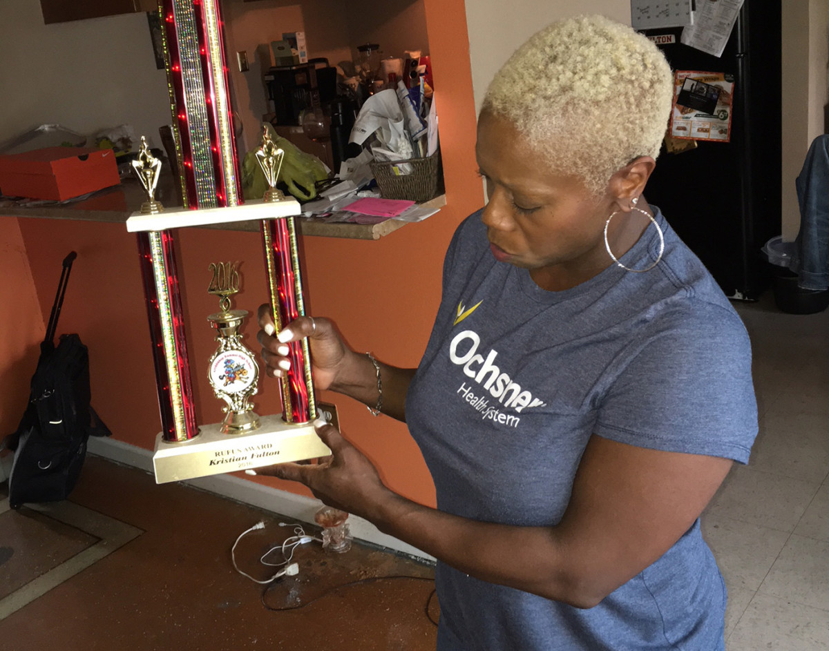 Michelle Fulton, Kristian's mother, holds a trophy her son won as a senior in high school.