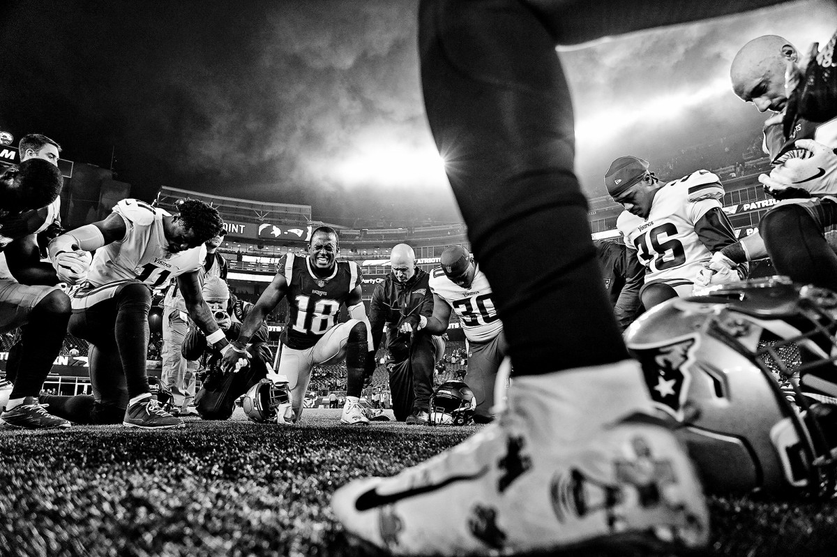 New England Patriots' Matthew Slater (18) with teammates and Minnesota Vikings players, praying in the endzone after a game at Gillette Stadium