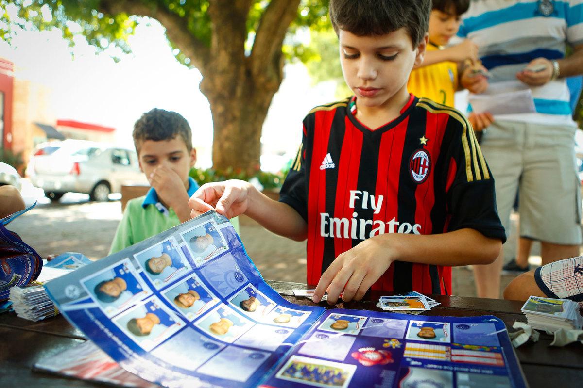 Cuiaba, Brazil, 2014: A kid checks his World Cup sticker album at Praça Popular.