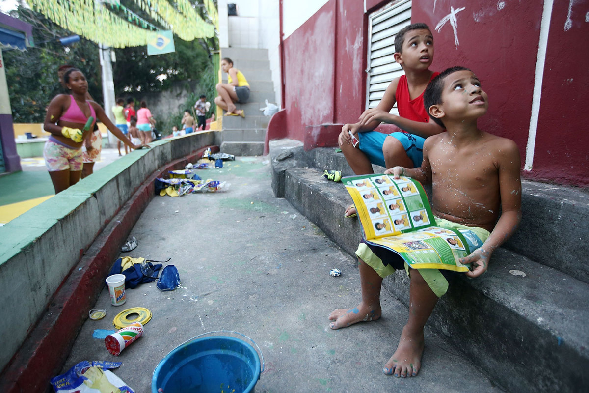 Rio de Janeiro, Brazil, 2014.Brazilians gather while painting a section of the Santa Marta favela in Brazilian colors as a boy holds his Panini World Cup sticker album.