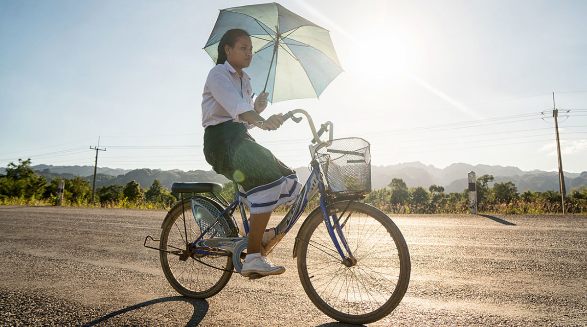 A schoolgirl cycling in Laos.