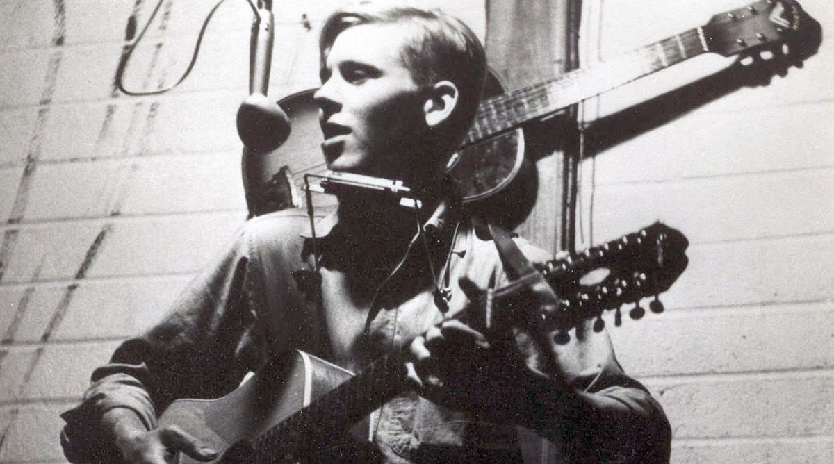 Stephen Rusch playing guitar, singing, and playing harmonica. Circa 1960s