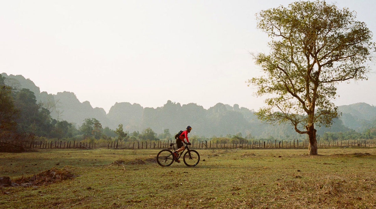 Rebecca cycling across a field in Laos. From the ride along the Ho Chin Minh Trail in 2015.