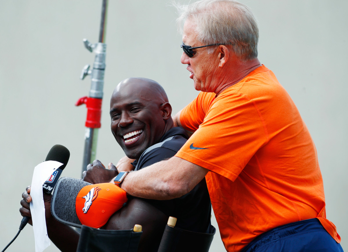 John Elway messes around with former teammate and current NFL Network analyst Terrell Davis during Broncos camp on Sunday.
