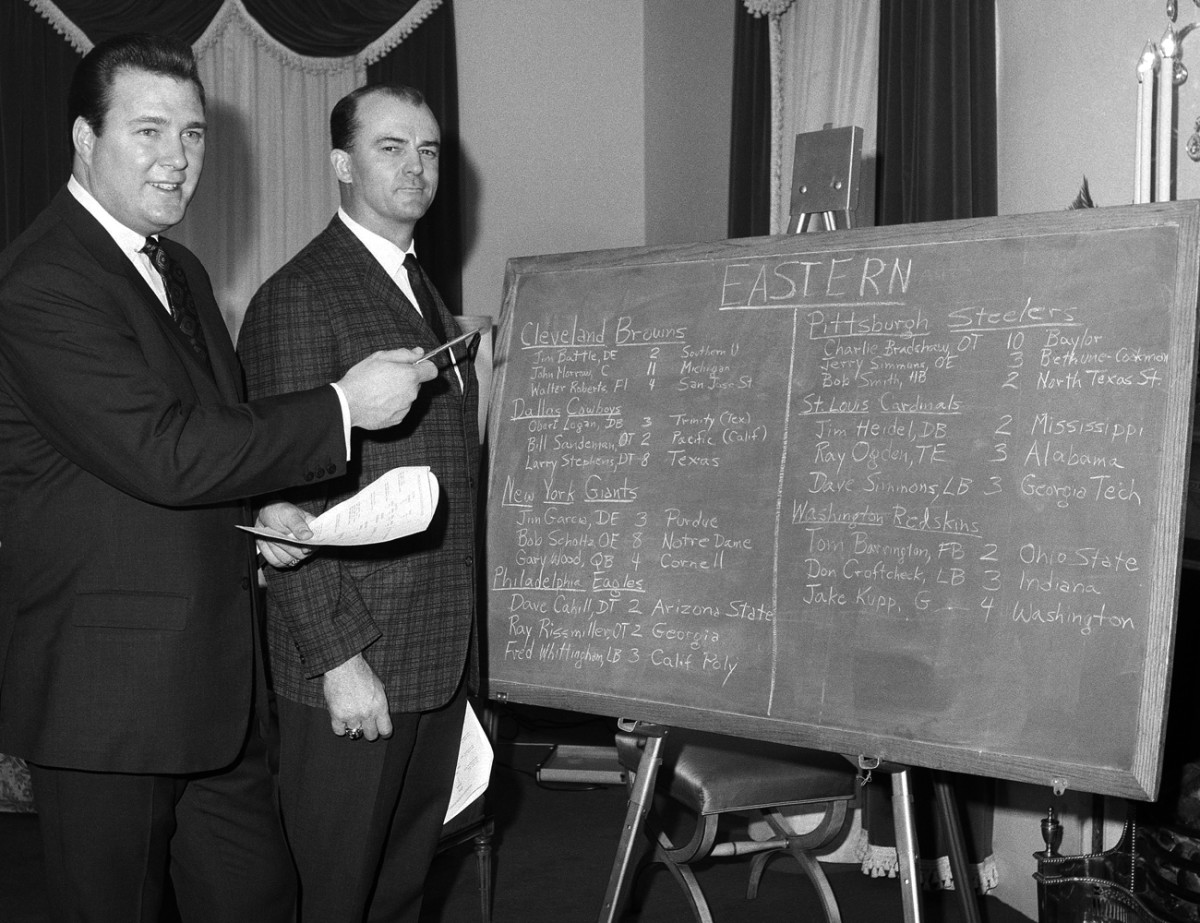 Owner John Mecom and coach Tom Fears check out expansion draft board, February 1967.