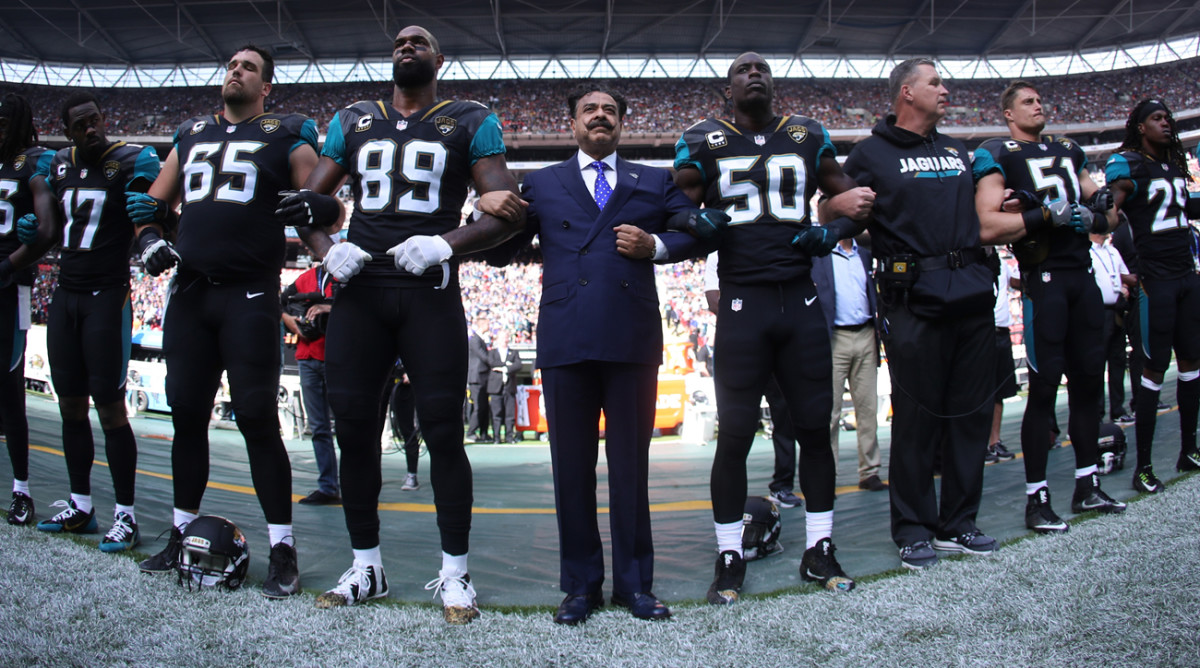 Jaguars owner Shad Khan locks arms with players during the national anthem on Sunday.