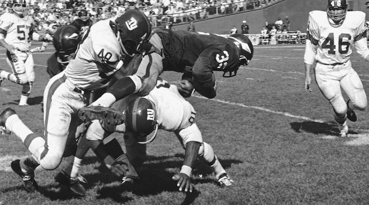 Ray McDonald (No. 32) leaps over Giants' Freeman White.