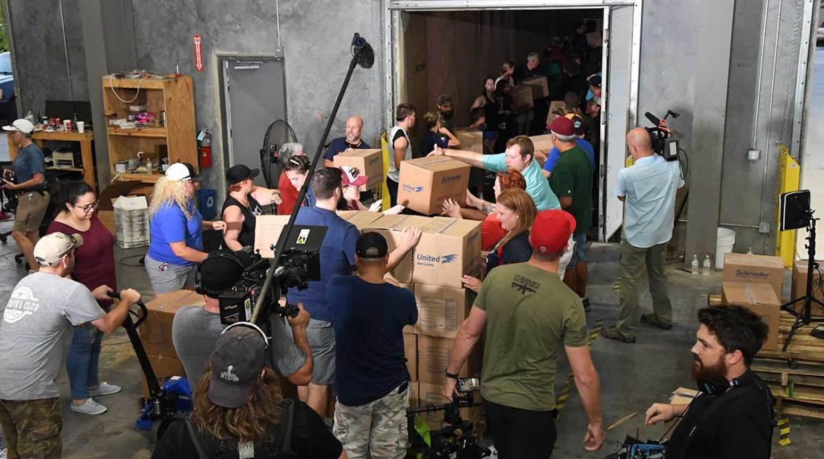 Volunteers help load trucks on Sunday.
