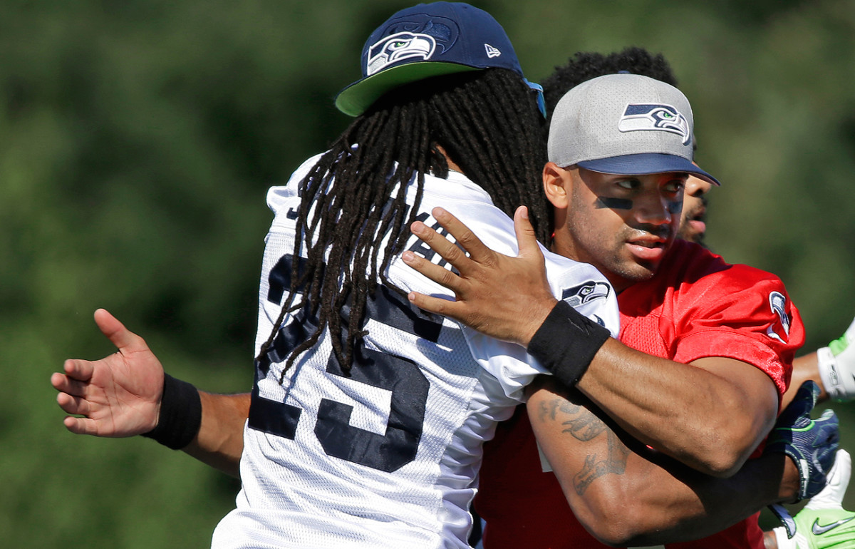 Richard Sherman and Russell Wilson are showing love here, but it hasn't been all hugs at Seahawks training camp so far.