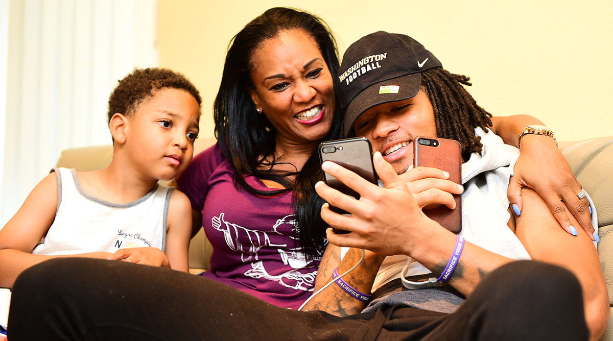 Sidney Jones keeping a close eye on his two phones with his mother and his brother.