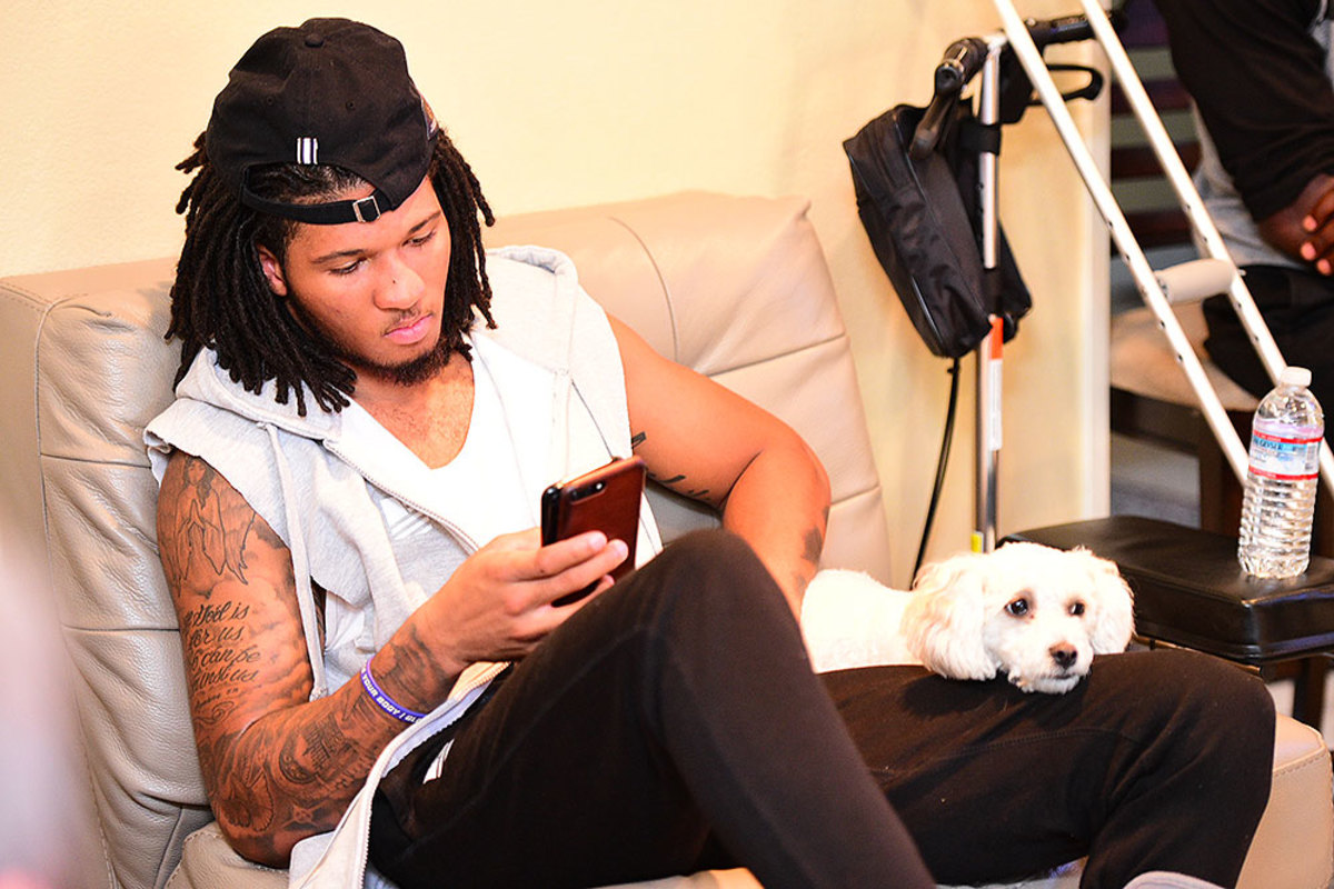 Sidney Jones checks out his two phones with his dog, Zyha.