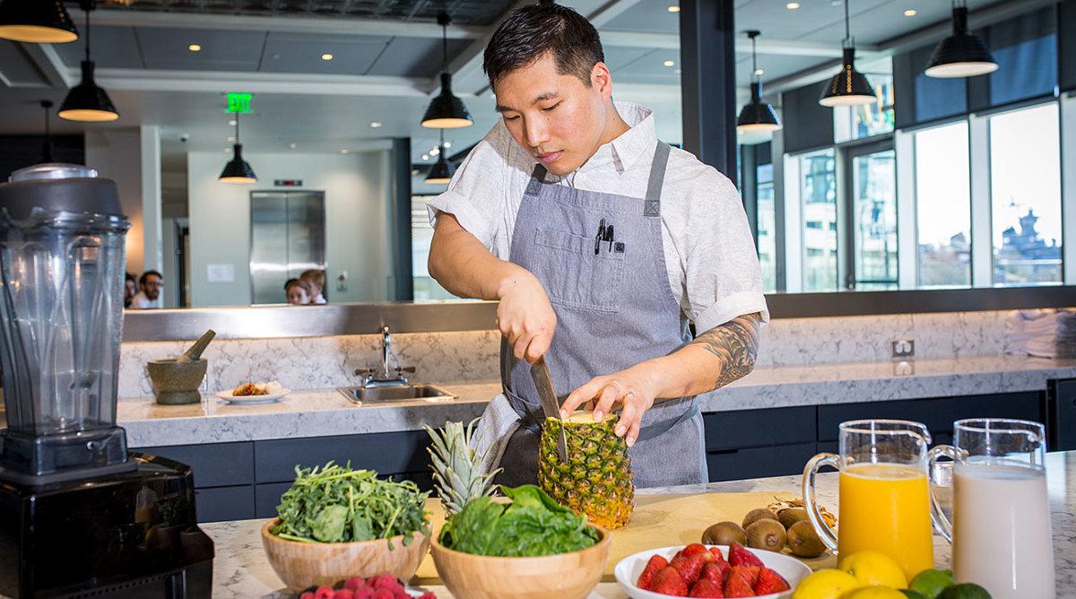 76ers executive chef JaeHee Cho slices a pineapple.