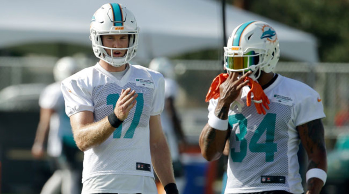 Ryan Tannehill (17) discusses a play with Arian Foster.