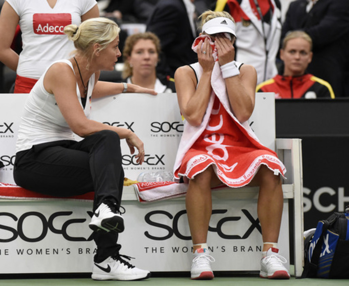Angelique Kerber of Germany, right,  sits besides German team captain Barbara Rittner, left, during her match against Belinda Bencic of Switzerland at the Fed Cup World Group first round tennis match between Germany and Switzerland at the Leipzig Fair in