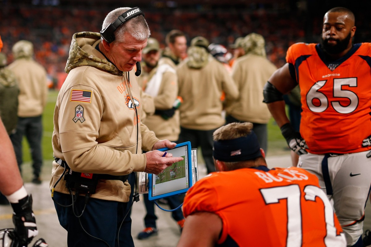 Denver Broncos offensive line coach Mike Munchak goes over a play with offensive tackle Garett Bolles (72) in the fourth quarter against the Cleveland Browns at Empower Field at Mile High.