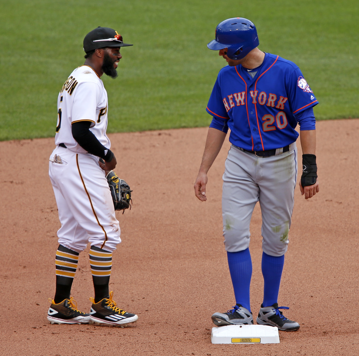 Former teammates New York Mets second baseman Neil Walker (20) and Pittsburgh Pirates second baseman Josh Harrison visit during the fourth inning of a baseball game in Pittsburgh, Tuesday, June 7, 2016. (AP Photo/Gene J. Puskar)