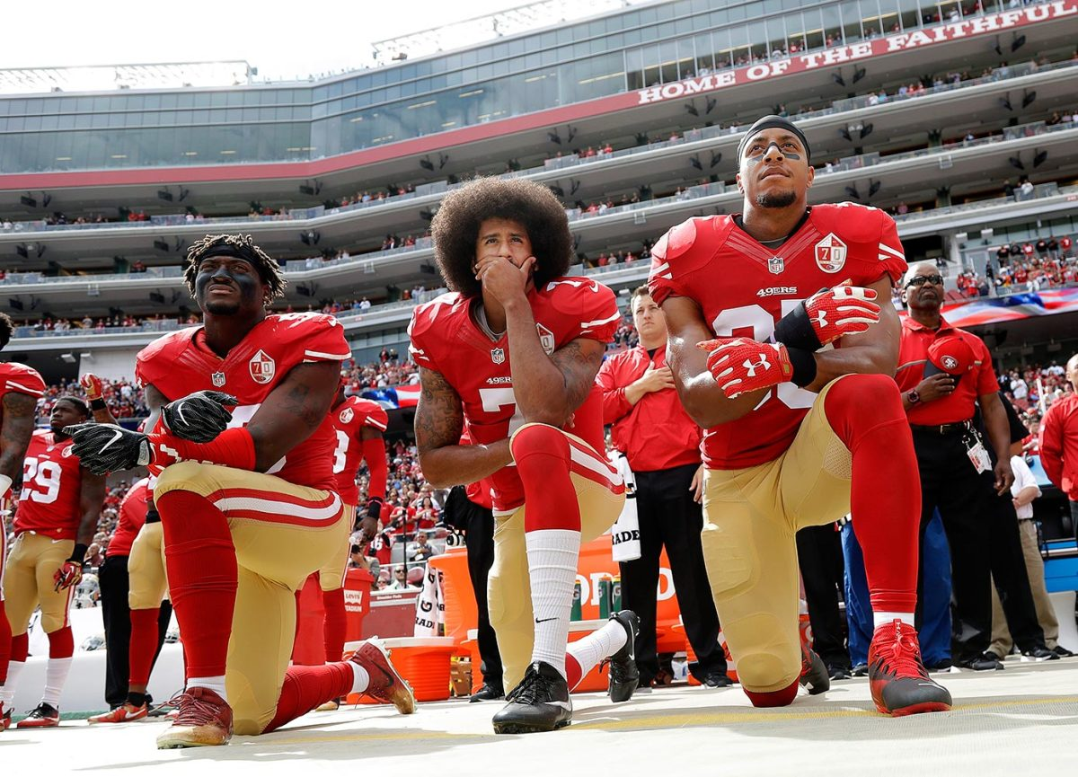 Eli Harold, Colin Kaepernick and Eric Reid kneeling during the national anthem before a San Francisco 49ers game in 2016.
