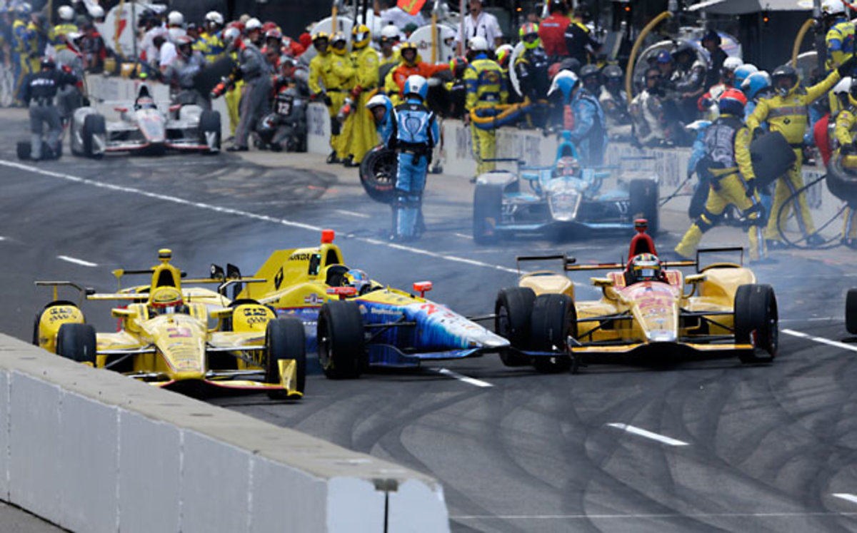 Helio Castroneves, left, Townsend Bell, center, and Ryan Hunter-Reay collide as they exit the pit area.