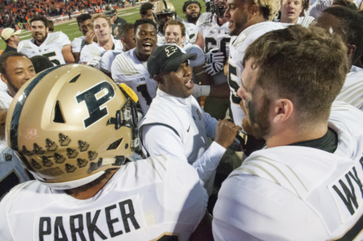Purdue head coach Darrell Hazell, center, celebrates an overtime victory with the team after an NCAA college football game against Illinois Saturday, Oct. 8, 2016, in Champaign, Ill.  Purdue defeated Illinois 34-31 in overtime.  (AP Photo/Bradley Leeb)