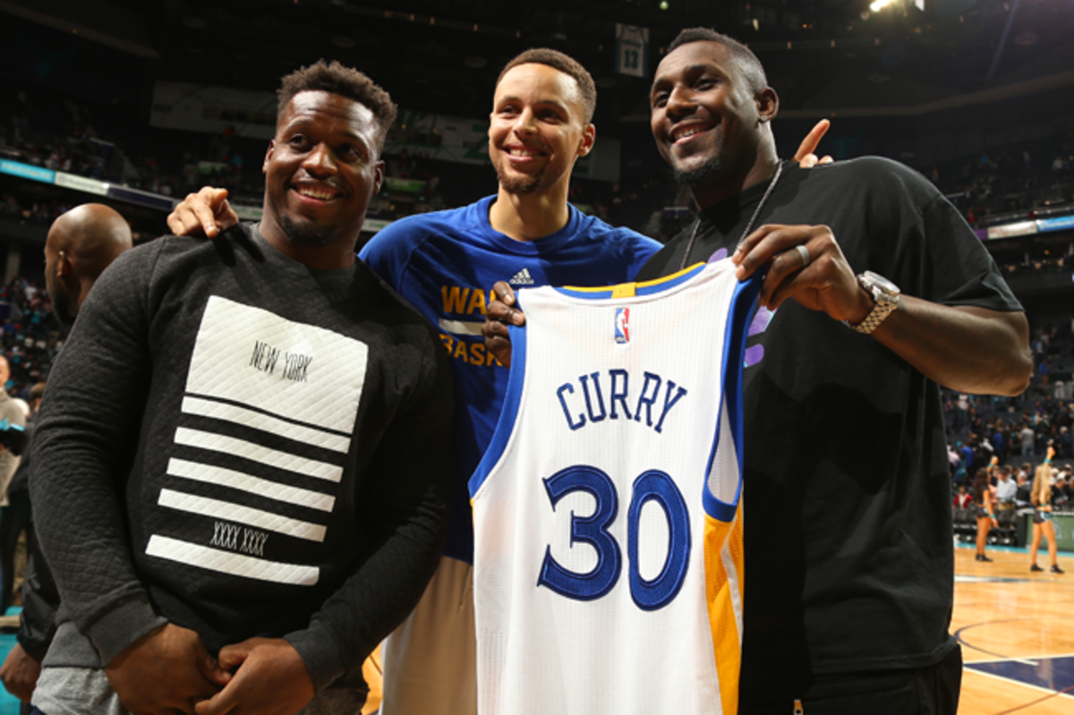 Jonathan Stewart (l.) and Thomas Davis meet with Stephen Curry after the Warriors beat the Hornets on Dec. 2.