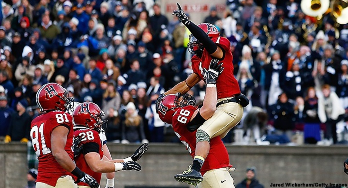 BOSTON, MA - NOVEMBER 22:  Andrew Fischer #1 of the Harvard Crimson is lifted in the air by teammate Michael Mancinelli #66 following Fischer's game-winning touchdown in the fourth quarter against the Yale Bulldogs during the game at Harvard Stadium in th