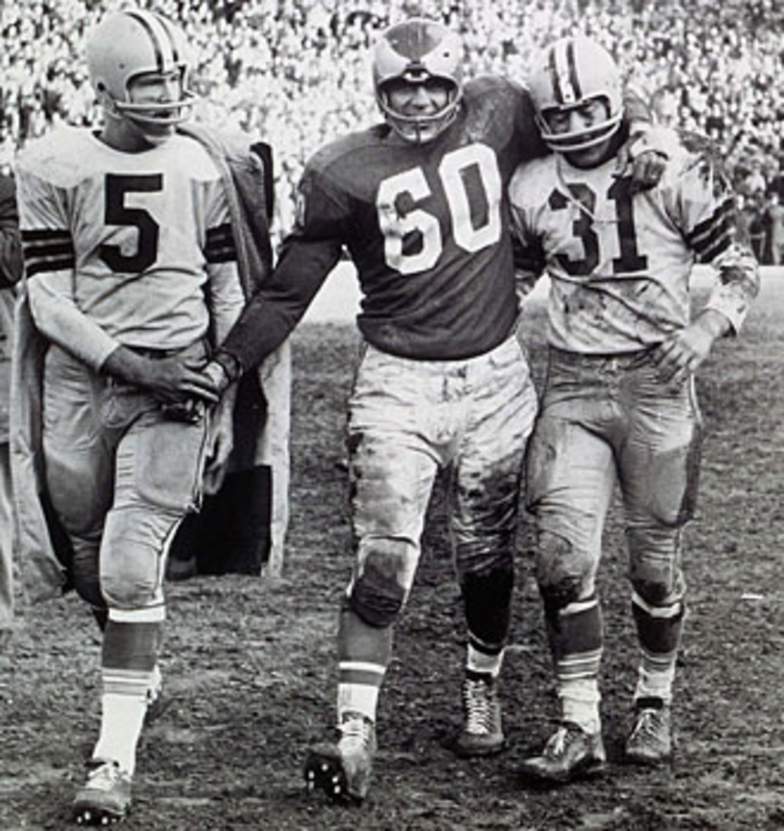 After nailing down the 1960 NFL title, Bednarik consoled Green Bay's Paul Hornung (left) and Jim Taylor.