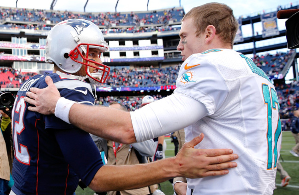 Tom Brady and Ryan Tannehill. Guess who got the better deal? (Jim Rogash/Getty Images)