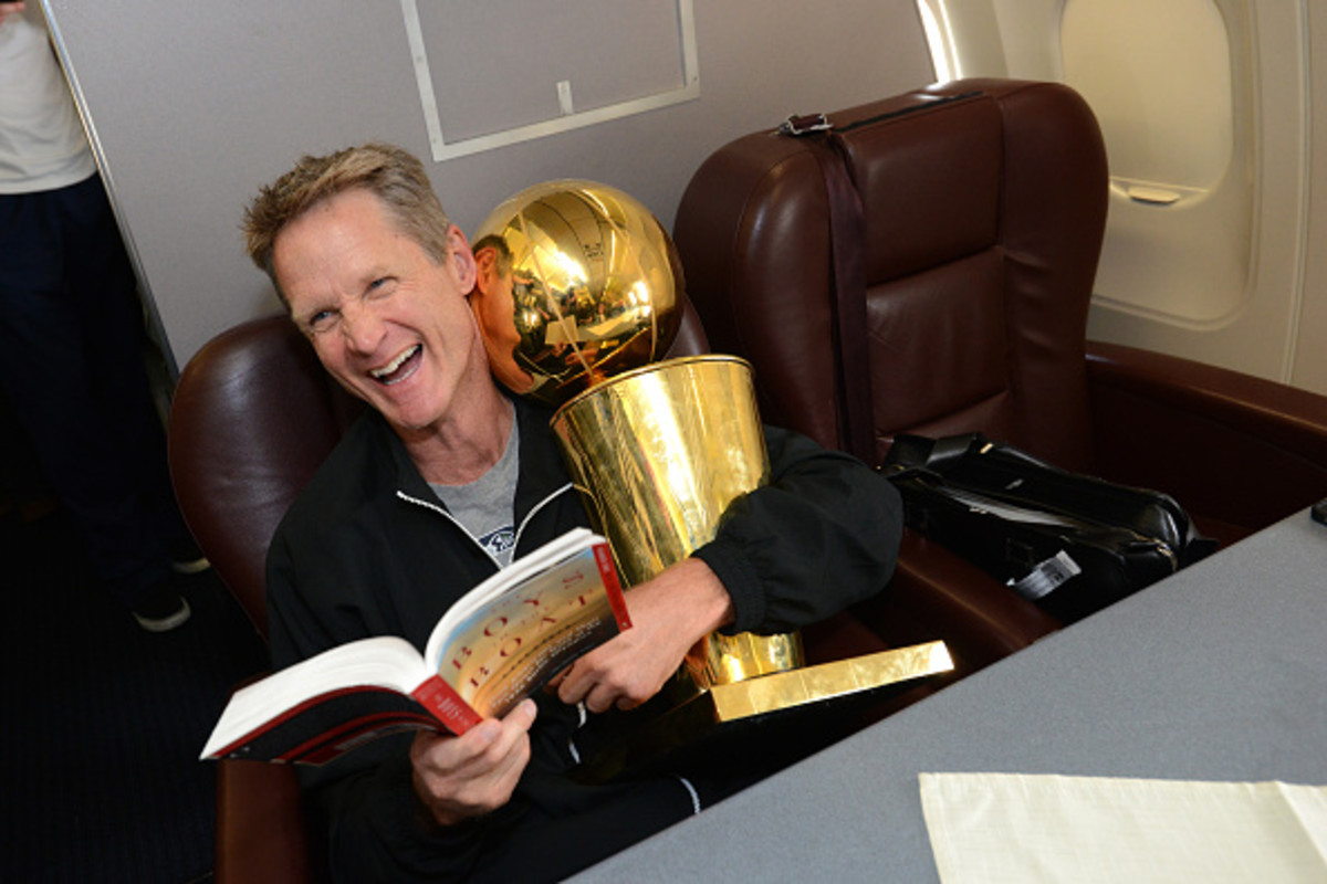 OAKLAND, CA - JUNE 17:  Steve Kerr of the Golden State Warriors holds the NBA trophy on the plane as the team travels home from Cleveland after winning the 2015 NBA Finals on June 17, 2015 in Oakland, California. (Photo by Noah Graham/NBAE via Getty Image