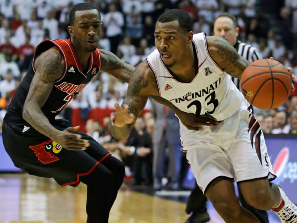 Russ Smith (left) and Louisville squeaked by Sean Kilpatrick and Cincinnati late. (Al Behrman/AP)
