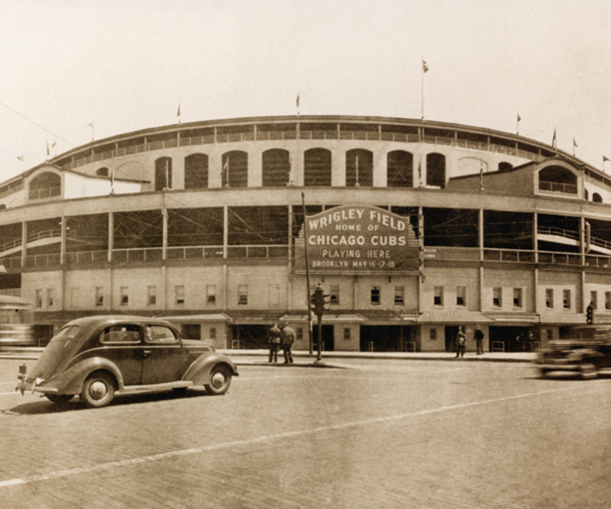 Exterior view of Wrigley Field as cars and pedestrians pass on the street in front of it, Chicago, Illinois, May 1939. (Photo by Photo File/Getty Images)